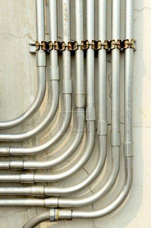 Photo pour Tubes en aluminium pour la protection des fils alignés sur un vieux mur en béton . - image libre de droit