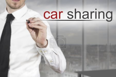 businessman writing car sharing in the air