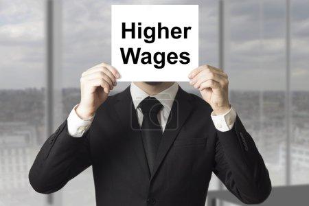 Photo pour Homme d'affaires en costume noir se cachant face derrière signe grève des salaires plus élevés - image libre de droit