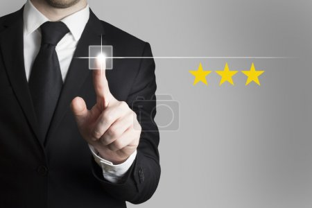 Businessman pushing button three rating stars