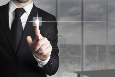 businessman in suit pushing small touchscreen button