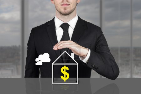 Businessman holding protective hand above house dollar symbol