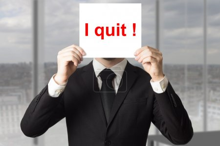 businessman hiding face behind sign i quit