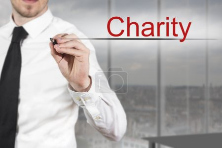 businessman in office writing charity in the air
