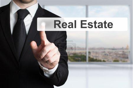 Photo pour Homme d'affaires dans la salle de bureau en poussant le bouton immobilier - image libre de droit
