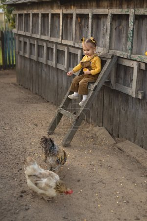A child in overalls sits high on the stairs and fe...