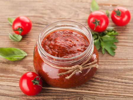 Photo for Tomato sauce (jam) with basil in glass jar, selective focus - Royalty Free Image