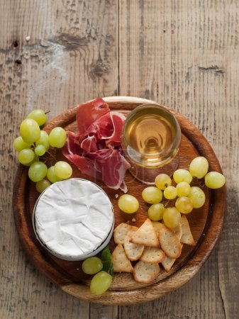 Camembert (brie) cheese on cutting board with wine...