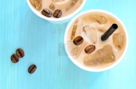 Photo for Iced coffee with milk or cream in paper one-off cups with a straws, top view - Royalty Free Image