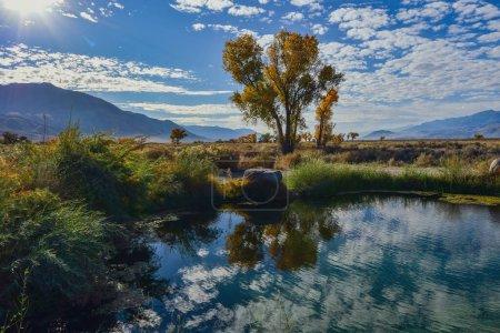 Photo pour Arbres d'automne reflétés dans l'eau de l'étang dans le paysage de vallée avec des nuages blancs dans le ciel bleu - image libre de droit