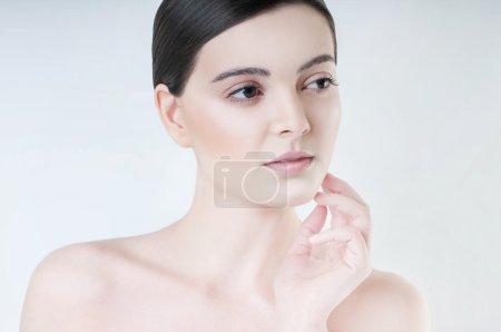 Photo pour Femme brune avec une peau propre et fraîche touchant son visage . - image libre de droit