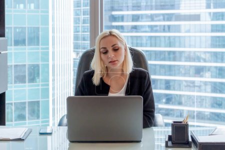 Photo for Beautiful caucasian woman with blond hair sits on chair in office and works using laptop. Blurred office buildings are visible in the background. Theme of Successful women in business. - Royalty Free Image