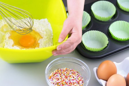 Photo pour Garçon ou fille Cuire des gâteaux de cuisson sur le point de fouetter l'oeuf dans la farine - image libre de droit