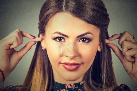 Photo pour Lutte contre le bruit. Jeune femme avec des bouchons d'oreille isolé sur fond de mur gris - image libre de droit