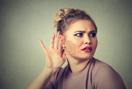 nosy woman hand to ear gesture carefully secretly listen in on gossip conversation