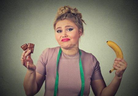 Photo pour Femme à l'air confus avec chocolat et banane essayant de faire un choix sain contrôler son poids corporel isolé sur fond de mur gris. Expression du visage humain - image libre de droit