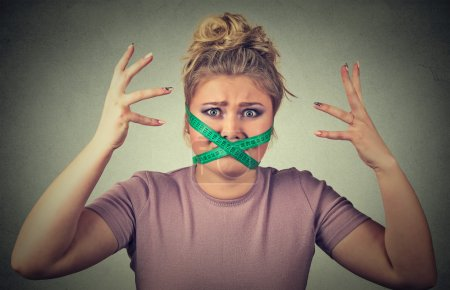 Frustrated woman with measuring tape around her mouth. Diet restriction and stress