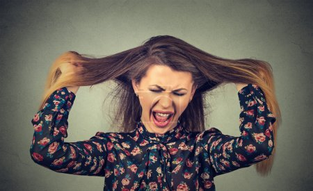 Photo for Very angry woman pulling her hair out screaming - Royalty Free Image