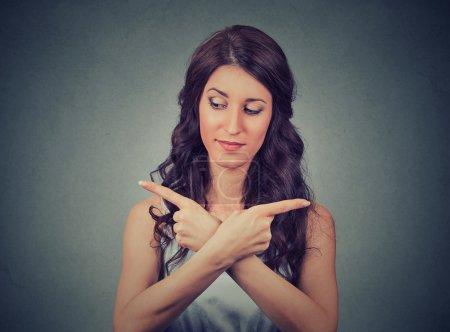 Photo pour Confus jeune femme pointant dans deux directions différentes ne sait pas quelle direction aller dans la vie. Émotion humaine expression faciale sentiment corps langage perception - image libre de droit