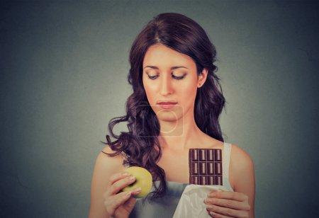 Photo pour Femme à l'air confus avec du chocolat et de la pomme essayant de faire un choix sain contrôler son poids isolé sur fond de mur gris. L'expression du visage humain. Concept de régime - image libre de droit