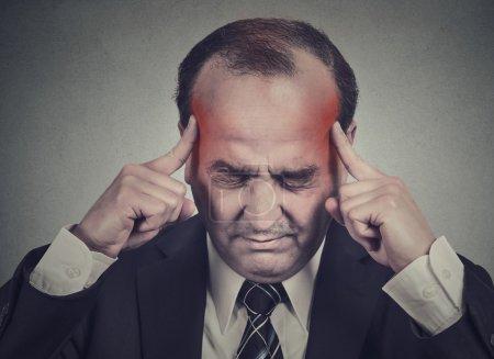 Foto de Closeup Retrato hombre envejecido medio piensa muy intensamente tener templos de dolor de cabeza coloreadas en rojo aislado sobre fondo de pared gris. Preocupado por la expresión de la cara tensionada. Emociones humanas - Imagen libre de derechos