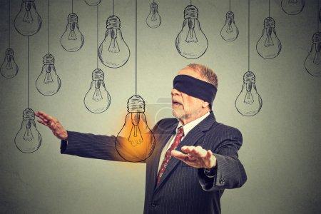 Photo pour Homme âgé les yeux bandés marchant à travers les ampoules à la recherche d'une idée lumineuse isolée sur fond de mur gris - image libre de droit