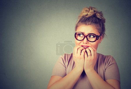 nervous stressed young nerdy woman in glasses biting fingernails looking anxiously