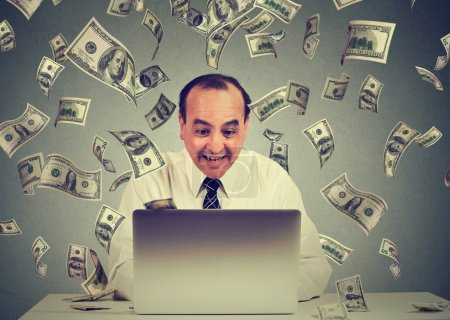 Photo for Middle aged business man using a laptop building online business making money dollar bills cash falling down. Money rain beginner IT entrepreneur success economy concept - Royalty Free Image
