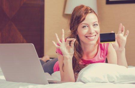 Photo pour Femme faisant du shopping en ligne tenant montrant carte de crédit donnant ok signe. Joyeux jeune femme couchée dans un lit dans sa chambre d'hôtel. Concept de satisfaction client - image libre de droit