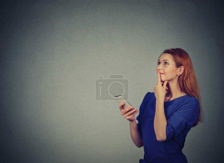 Photo pour Belle femme textos sur son téléphone mobile en regardant la planification isolé sur fond de mur gris avec espace de copie - image libre de droit