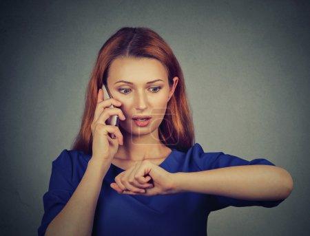 Mujer de negocios sorprendida estresada mirando el reloj de pulsera, llegando tarde