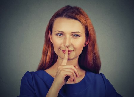 secretive young woman placing finger on lips asking shh, quiet, silence