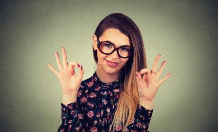 Photo pour Belle jeune femme heureuse dans des lunettes montrant Ok signe isolé sur fond de mur gris. Émotions humaines positives expression du visage langage corporel geste - image libre de droit