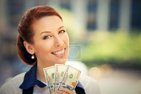 Photo pour Closeup portrait heureux heureux succès jeune fortunée détient une somme billets d'un dollar dans la main en regardant caméra isolée à l'extérieur de fond. Expression faciale des émotions positives. Récompense financière - image libre de droit