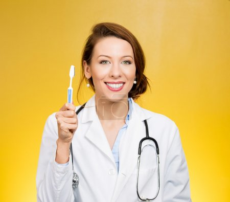 Photo for Smiling dentist with toothbrush isolated on yellow background - Royalty Free Image