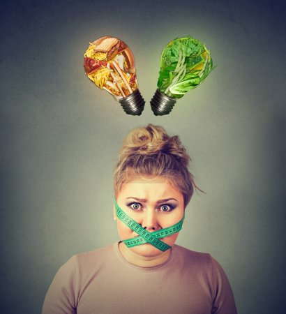 Diet restriction stress. Frustrated woman with measuring tape around her mouth