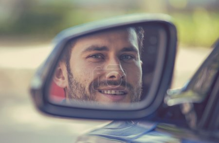 Man driver looking in car side mirror, making sure line is free before making turn