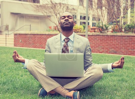 Photo pour Young businessman with laptop meditating in lotus pose taking a deep breath outside corporate office. Business yoga and stress free environment. Peace of mind concept - image libre de droit