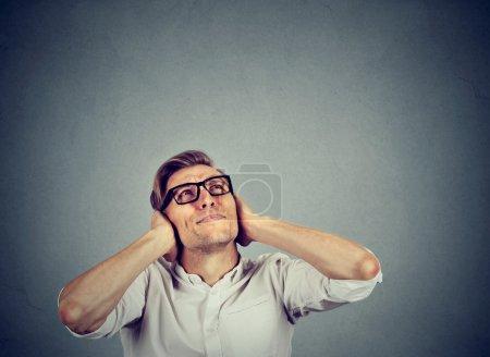 Photo pour Jeune homme agacé, malheureux, stressé, couvrant ses oreilles, levant les yeux, arrêtant de faire du bruit fort, me donnant mal de tête isolé sur fond gris avec de l'espace de copie. Réaction émotionnelle négative - image libre de droit