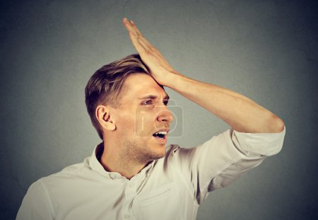 silly man, slapping hand on head having duh moment regrets