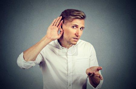 Photo pour Malheureux dur d'homme audience posant la main sur l'oreille demander à quelqu'un de prendre la parole ou l'écoute de mauvaises nouvelles, isolé sur fond gris. Sentiments d'expression faciale des émotions négatives. - image libre de droit