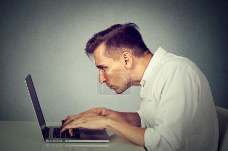 Photo pour Jeune homme de côté profil travaillant sur ordinateur, assis au bureau isolé sur fond de bureau mur gris. Concept de vie longtemps monotone du fastidieux travail heures - image libre de droit