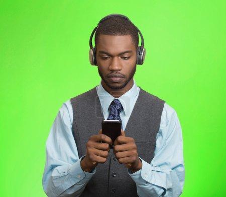 Businessman with headphones browsing internet on smart phone