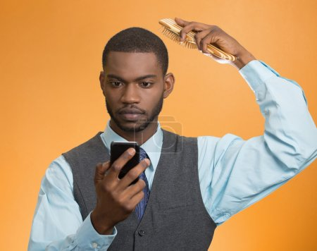 man reading news on smart phone combing his hair