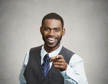 Photo pour Gros plan portrait jeune homme heureux, riant, pointant du doigt quelqu'un, quelque chose, fond de mur gris isolé. Expressions positives du visage humain émotion, sentiments, attitude, approche, perception - image libre de droit