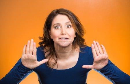Photo pour Portrait prudent, effrayé, agacé jeune femme mécontente levant la main pour dire non, arrêtez-vous juste là fond orange isolé. Émotion humaine négative symbole de signe d'expression faciale - image libre de droit