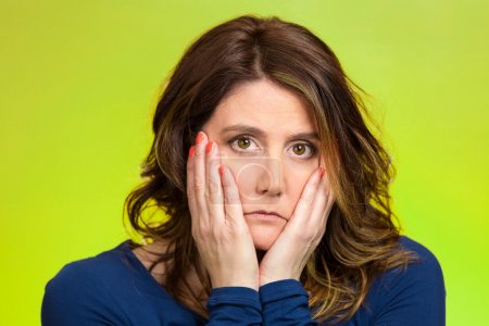Photo for Closeup portrait sad, depressed, stressed, thoughtful middle aged woman, full of worries, confused, lost isolated green background. Human face expressions, emotions, feeling reaction attitude, body language - Royalty Free Image