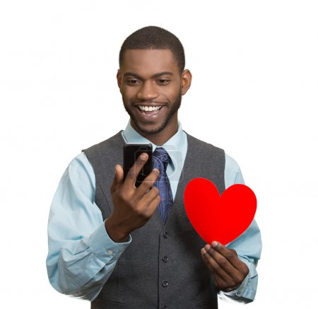 Man looking at his smart phone, holding red heart in hand