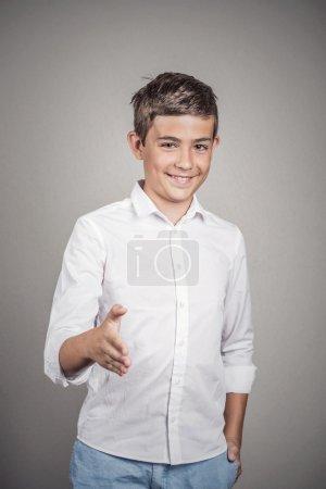 Photo pour Beau jeune homme souriant donnant des bras qui se prolongent pour la poignée de main au fond de caméra geste isolé mur gris. des émotions humaines positives, sentiments, expressions du visage, langage corporel - image libre de droit