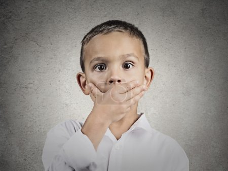 Photo for Closeup portrait child astonished face expression, covering mouth with hand, wide open eyes, isolated grey wall background. Human emotions, body language, perception. Unexpected discovery, reaction - Royalty Free Image